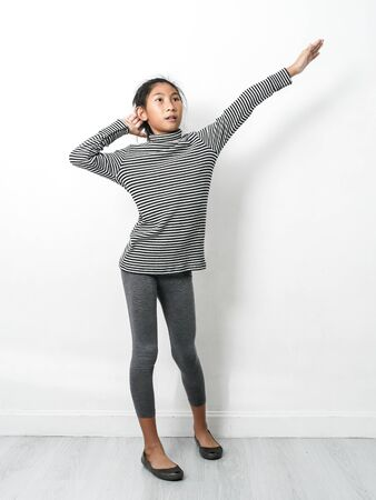 Asian girl wearing turtle neck, skinny dancing with white wall, lifestyle concept.