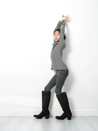 Asian girl wearing turtle neck, skinny and long boots with white wall and gray wooden floor, fashion concept.