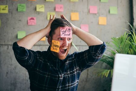 Stressed man with message on sticky notes over his face in office. Foto de archivo