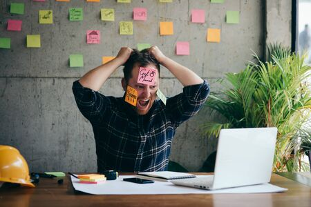Stressed man with message on sticky notes over his face in office.