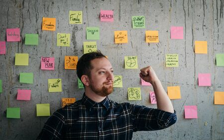 Happy engineer man present his sticky notes chart on cement wall. Entrepreneur concept
