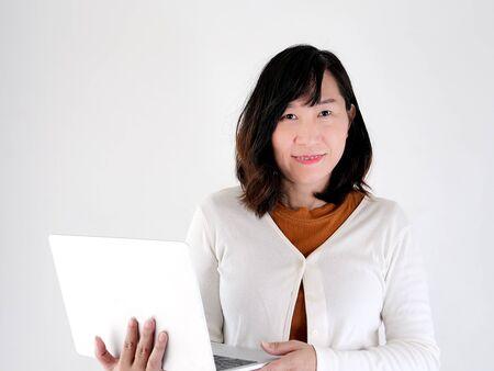 Heureuse femme asiatique utilisant un ordinateur portable contre le mur, concept de style de vie. Banque d'images