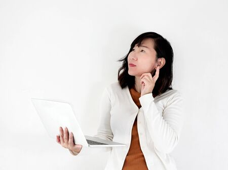Happy Asian woman using laptop against the wall, lifestyle concept. Stok Fotoğraf