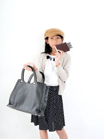Happy Asian girl wearing flatcap and holding leather bag, fashion concept.