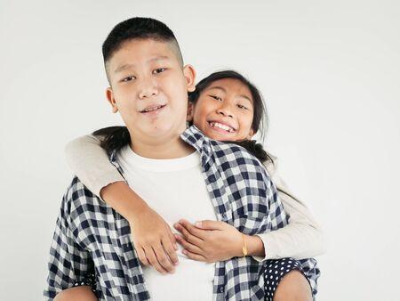 Felice bella ragazza asiatica che si diverte a cavalcare suo fratello sulle spalle, concetto di stile di vita. Archivio Fotografico
