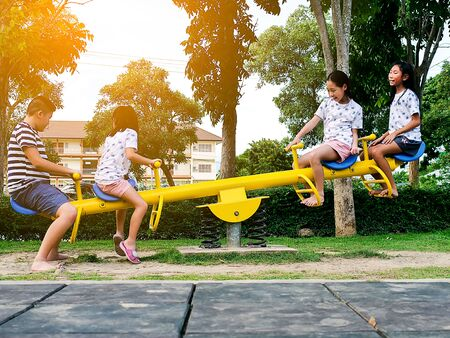 Happy Asian children playing seesaw board together in the park outdoor, lifestyle concept.