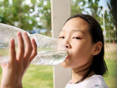 Asiatisches Mädchen, das eine Flasche Wasser im Freien trinkt.
