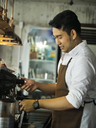 Happy Asian barista man working in cafe, lifestyle concept.