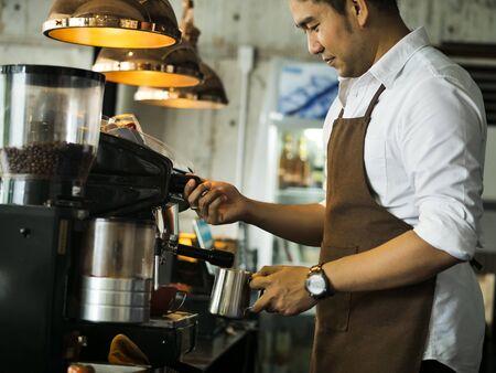 Szczęśliwy azjatycki barista człowiek pracujący w kawiarni, koncepcja stylu życia. Zdjęcie Seryjne