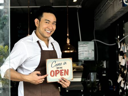 Cheerful Asian barista man holding welcome board in front of coffee shop.