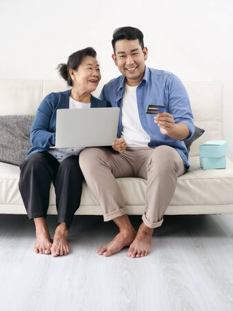 Asian man teaching his mother for shopping online, modern lifestyle concept.