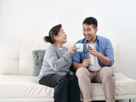 Asian mother and her son talking and drinking at home, lifestyle concept.