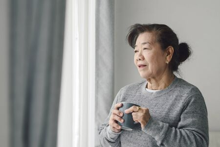 Asian senior woman drinking hot tea near window outdoor, lonely concept. Imagens