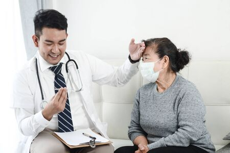 Asian doctor checking up his patient old woman in office.