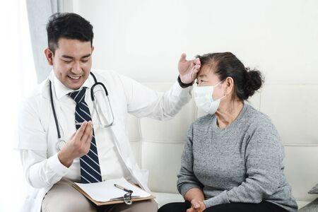 Medico asiatico che controlla la sua anziana paziente in ufficio. Archivio Fotografico