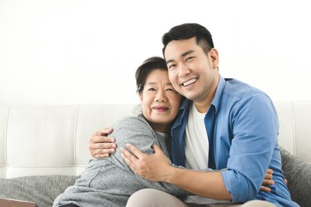 Asian mother hugging her son and sitting on sofa at home, lifestyle concept. 免版税图像