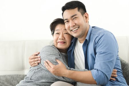 Asian mother hugging her son and sitting on sofa at home, lifestyle concept. 版權商用圖片
