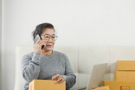 Asian senior woman taking order by phone ,online business with packaging and work at home concept.