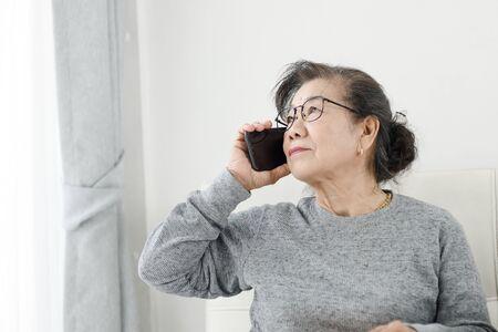 La donna anziana asiatica fa una telefonata bianca seduta sul divano di casa, concetto di stile di vita.