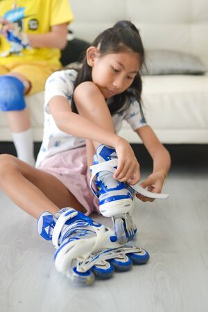 Happy Asian girls wearing protection set before playing roller skating, lifestyle concept.
