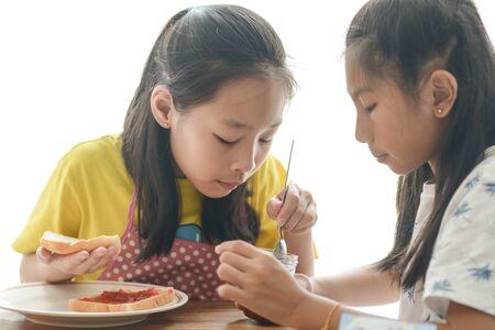 Asian sister spreading strawberry jam on bread for her younger sister. 版權商用圖片