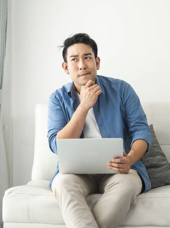 Stressed Asian man using laptop at home, lifestyle concept with copy space. Stockfoto