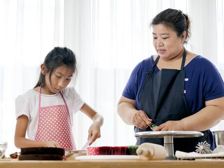 Asian girl learning with her mother preparing for decorate homemade cupcake, lifestyle concept.