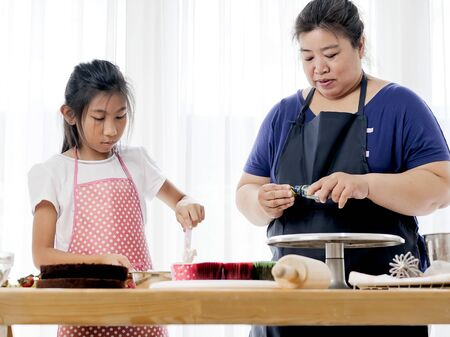 Asian girl help her mother preparing for decorate homemade cupcake, lifestyle concept.