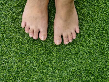 Feets on green grass background.