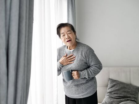 Asian senior woman having heart attack while staying at home alone, lifestyle concept. Banco de Imagens