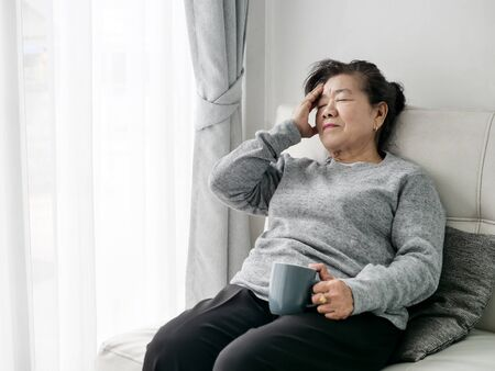 Asian senior woman having headache at home, health care concept. 版權商用圖片