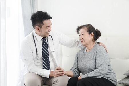 Aziatische arts die zijn geduldige oude vrouw op kantoor controleert.