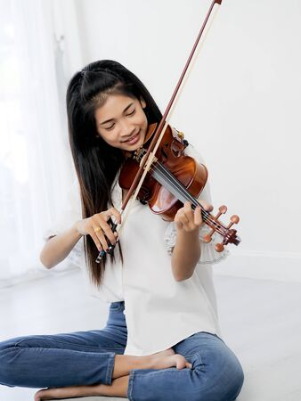 Asian teenager playing violin next to window, lifestyle concept.