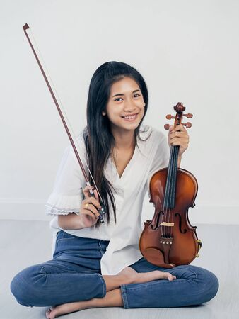 Beautiful Asian woman holding violin and sitting on the floor, lifestyle concept.