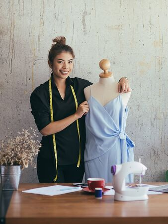 Confident freelance designer with cloth dummy in her workplace, lifestyle concept.