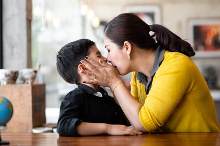 Asian mother kissing her son, lifestyle concept.
