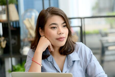 Asian woman using laptop and thinking something, lifestyle concept.
