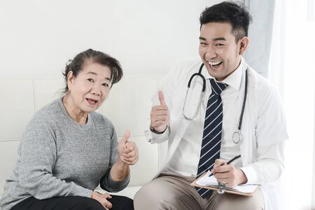 Asian doctor and senior patient with thumbs up hands sign, health care concept.