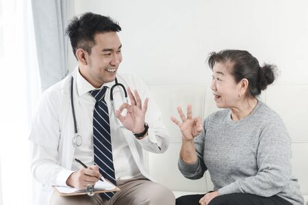 Asian doctor and senior patient with OKAY hands sign, health care concept.