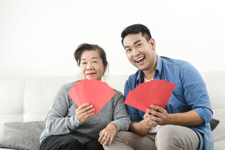 Happy Asian mother give red envelopes containing cash to her son for Chinese New Year concept.