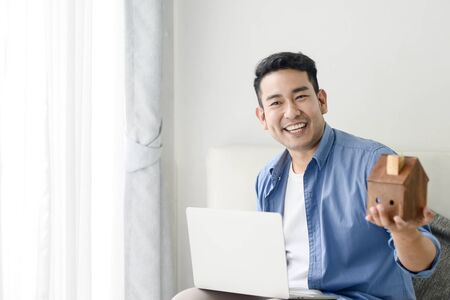 Asian man holding house in his hand and using laptop, real estate concept.