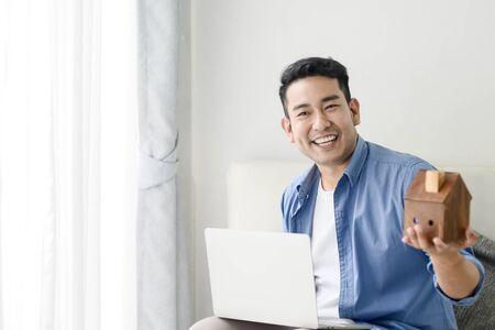 Uomo asiatico che tiene la casa in mano e usa il computer portatile, concetto di bene immobile. Archivio Fotografico