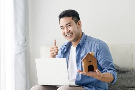 Asian man holding house in his hand and using laptop, real estate concept. Zdjęcie Seryjne - 129901049