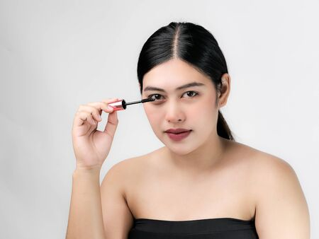 Close-up portrait of nice lovely cute sweet attractive  cheerful positive Asian woman holding in hands applying trendy black mascara isolated over gray background. Фото со стока