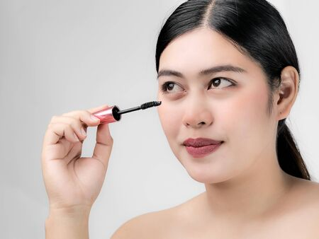 Close-up portrait of nice lovely cute sweet attractive  cheerful positive Asian woman holding in hands applying trendy black mascara isolated over gray background. Фото со стока - 129901213