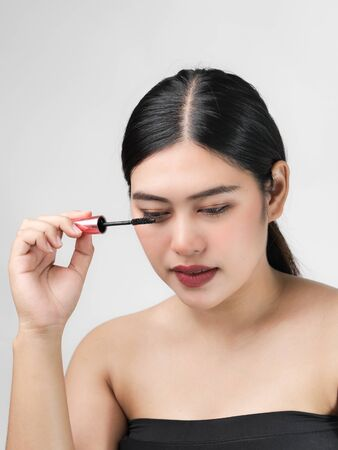Close-up portrait of nice lovely cute sweet attractive  cheerful positive Asian woman holding in hands applying trendy black mascara isolated over gray background. Фото со стока - 129901238
