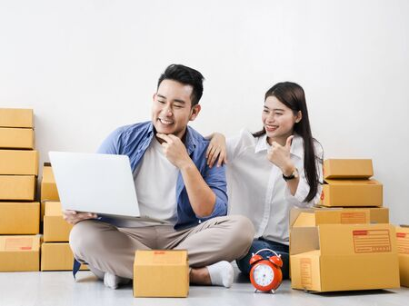 Asian couple with stack of parcel boxes, online business and delivery concept.