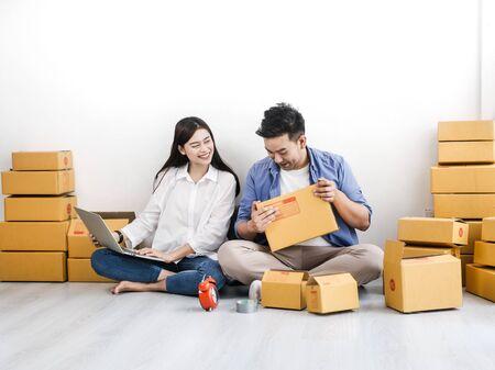 Aziatisch paar met stapel pakketdozen, online zaken en leveringsconcept.