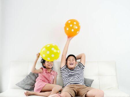 Hermana asiática y su hermano jugando globos juntos en casa, concepto de estilo de vida. Foto de archivo
