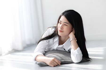 Beautiful Asian woman in white shirt relaxing on floor near window in the morning. Reklamní fotografie